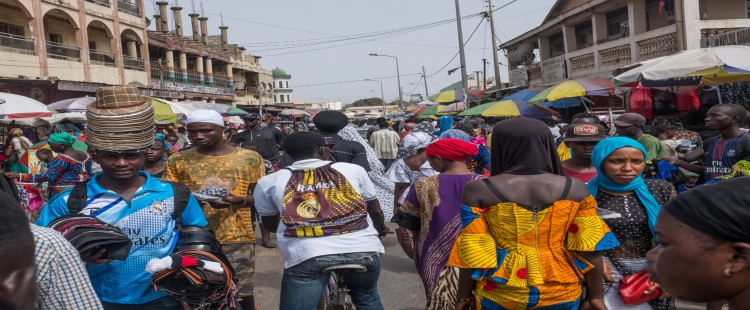 crowd of people walking through the streets in the gambia